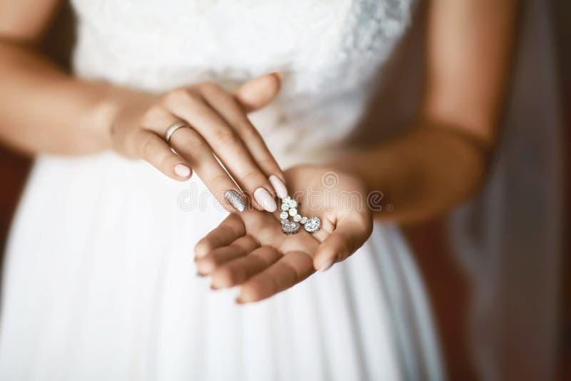 Orecchini di nozze su una mano nuziale, accessori di mattina e dei gioielli del ` s della sposa e concetto della decorazione immagini stock libere da diritti
