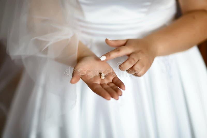 Orecchini di nozze su una mano nuziale, accessori di mattina e dei gioielli del ` s della sposa e concetto della decorazione fotografia stock