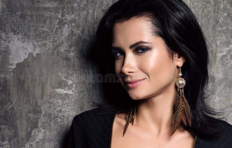 Orecchini e gioielli Ritratto del primo piano di giovane bella donna con capelli scuri immagini stock
