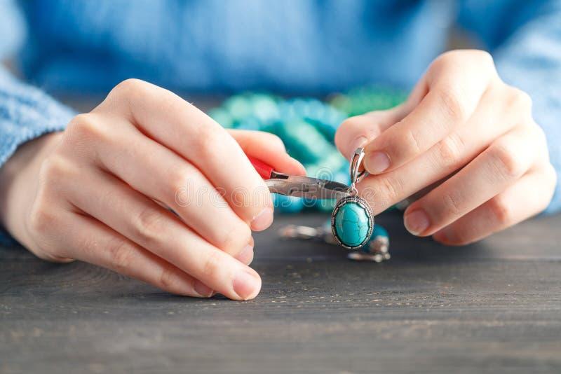 Orecchini fatti a mano che fanno, officina domestica L'artigiano della donna crea i gioielli della nappa Arte, hobby, concetto de fotografia stock libera da diritti