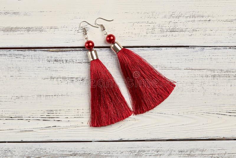 Orecchini rossi della nappa su fondo bianco fotografia stock