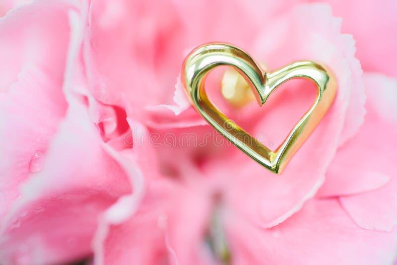 Orecchino del cuore sul fiore rosa fotografia stock libera da diritti