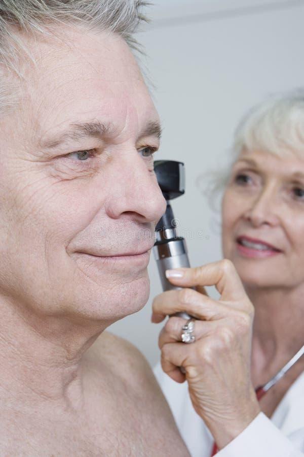Orecchio del dottore Examining Patient facendo uso dell'otoscopio immagine stock libera da diritti
