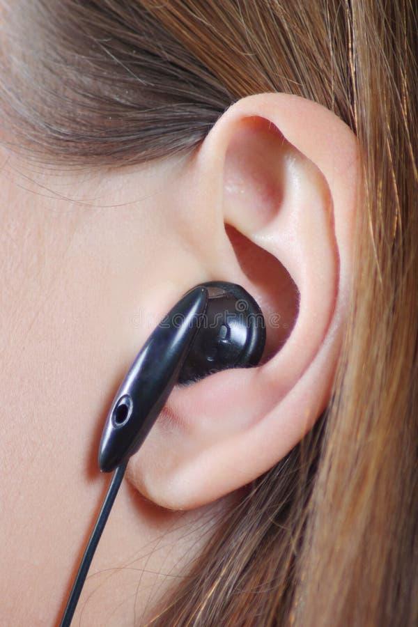 Orecchio femminile con un trasduttore auricolare immagine stock libera da diritti