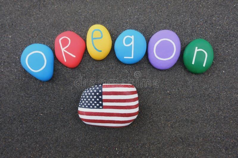 Oregon, Estados Unidos da América, lembrança com pedras coloridas e bandeira dos EUA sobre a areia vulcânica preta foto de stock