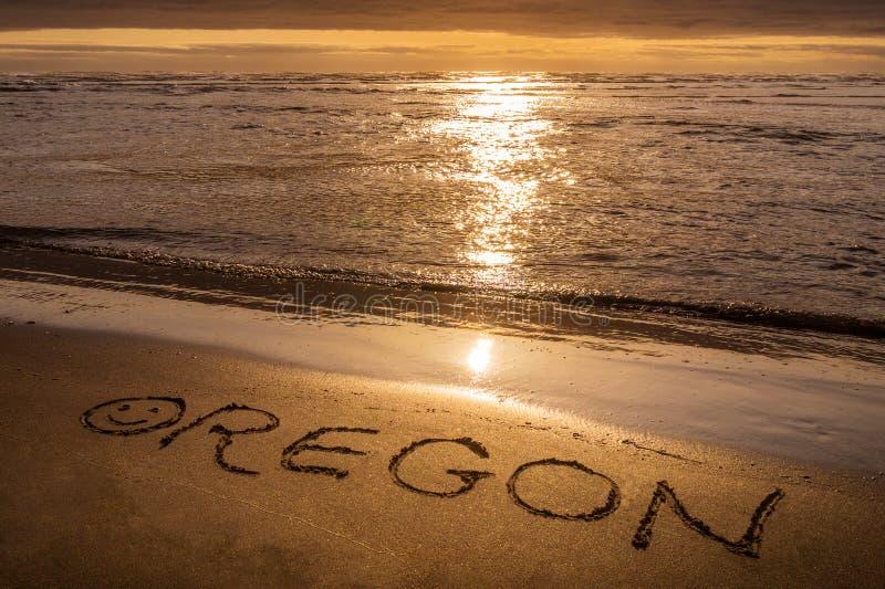 Oregon kustsolnedgång, text som är skriftlig på stranden arkivbilder