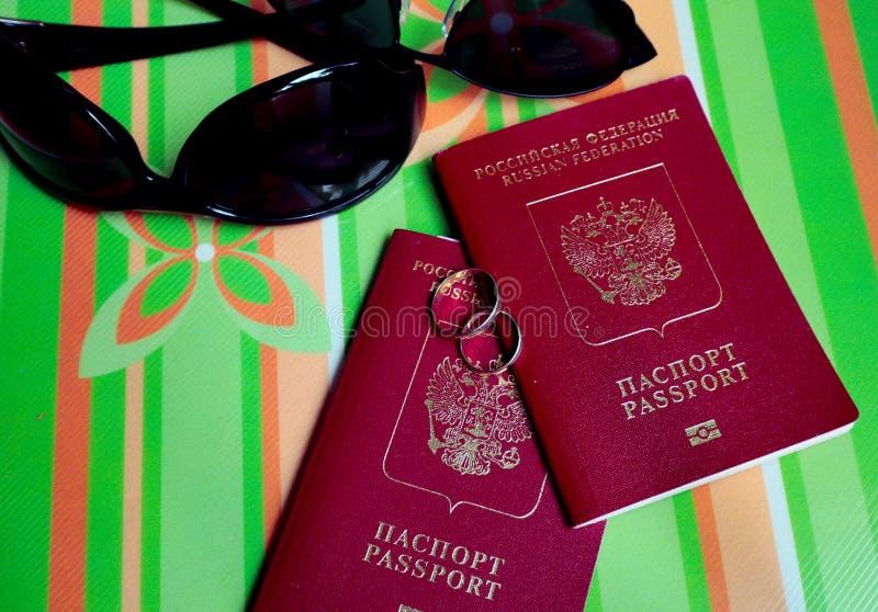 Oreign dois passaportes e duas alianças de casamento com óculos de sol em um fundo verde, viagem do casamento fotografia de stock