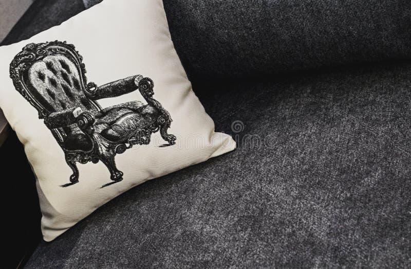 Oreiller blanc avec le modèle sur le sofa gris Repos, dormant, concept de confort Oreiller blanc avec le modèle de fauteuil photos libres de droits