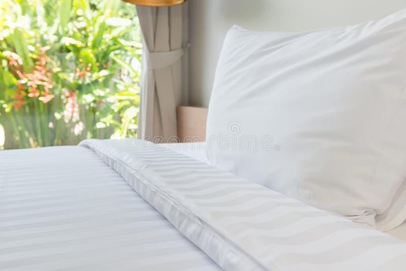 Oreiller blanc et lit blanc dans la chambre de lit photographie stock