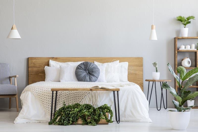 Oreiller bleu sur le lit blanc avec la tête de lit en bois dans l'interi de chambre à coucher photo stock