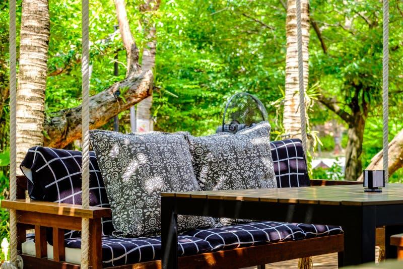 Oreiller coloré sur la chaise en bois avec le coussin de tissu dans le jardin à photographie stock