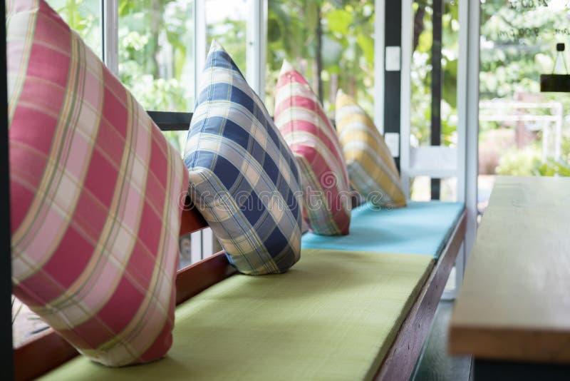 oreiller coloré sur la chaise en bois avec le coussin de tissu dans le restaurant image stock