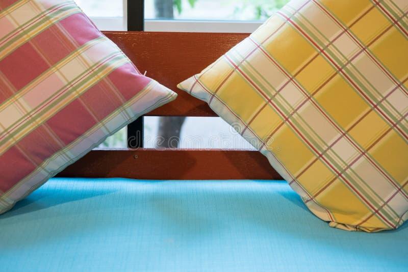 oreiller coloré sur la chaise en bois avec le coussin de tissu dans le restaurant photo stock