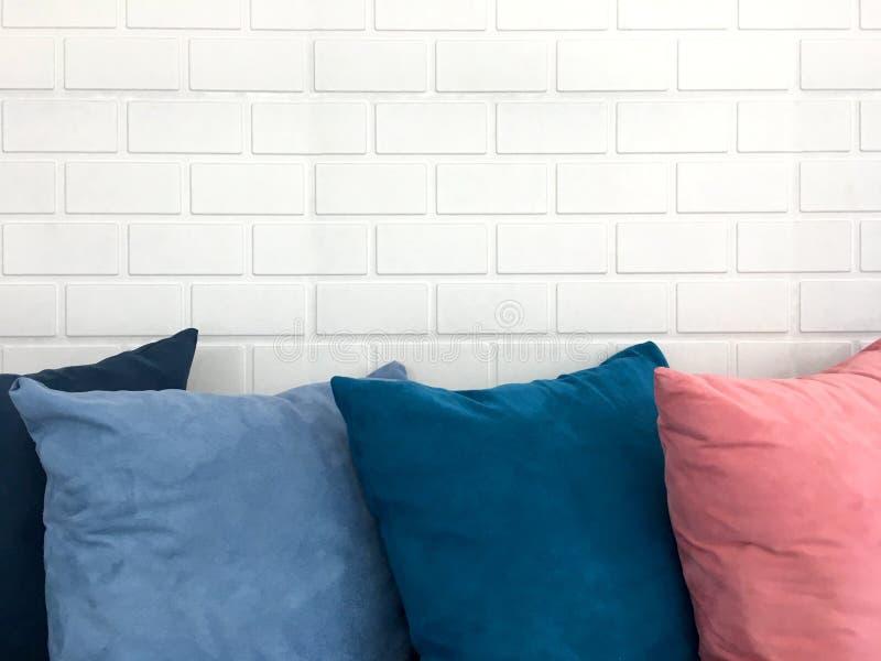 Oreiller de repos décoratif coloré sur le sofa devant le fond blanc de brique photographie stock libre de droits