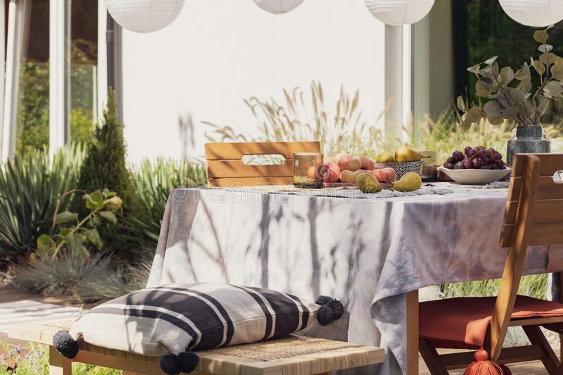 Oreiller modelé sur le banc en bois à la table avec des fruits sur la terrasse de la maison avec des usines images stock