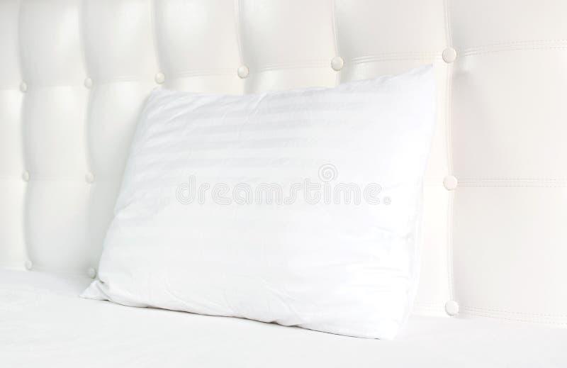 Oreiller piqu? blanc mol dans le lit sur le fond de la t?te de lit piqu?e en cuir blanche Oreiller propre, une partie de plan rap photo libre de droits