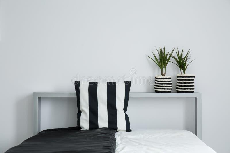 Oreiller rayé sur la couverture de lit noire et blanche image libre de droits