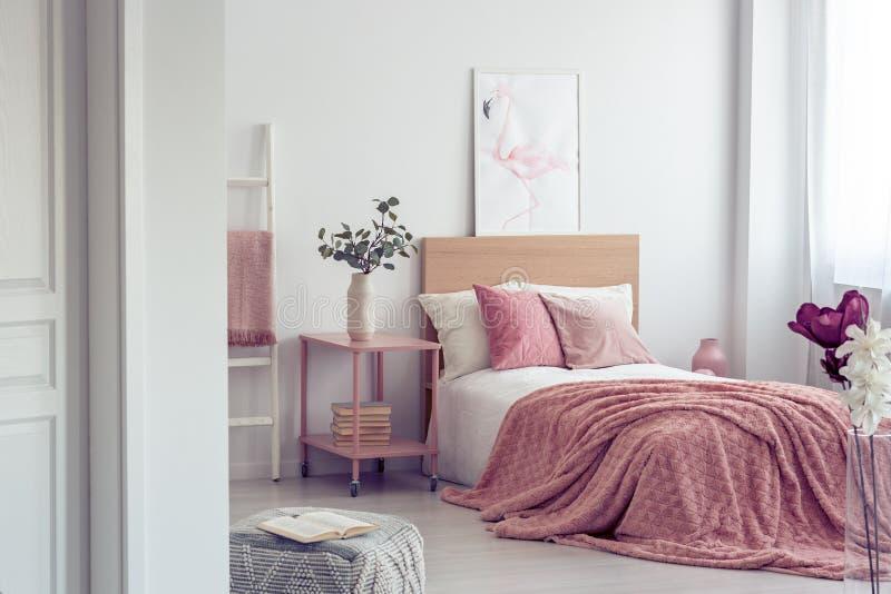Oreiller rose en pastel et couverture sur le lit en bois simple avec la literie blanche dans l'intérieur scandinave de chambre à  photos libres de droits