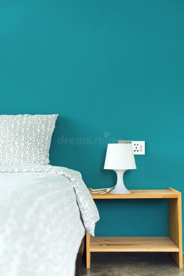 Oreiller sur la tête du lit et la lampe sur la table de chevet photos stock
