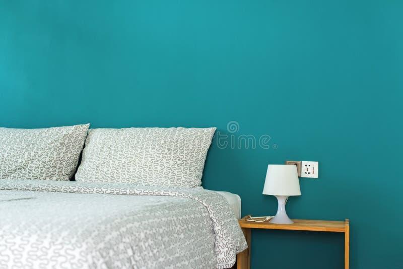Oreiller sur la tête du lit et la lampe sur la table de chevet photo libre de droits