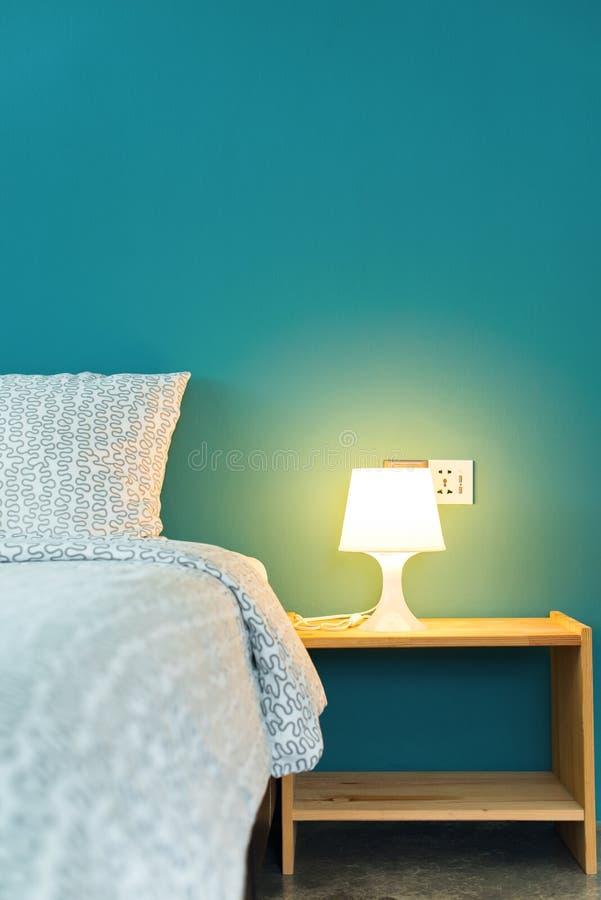 Oreiller sur la tête du lit et la lampe sur la table de chevet photo stock