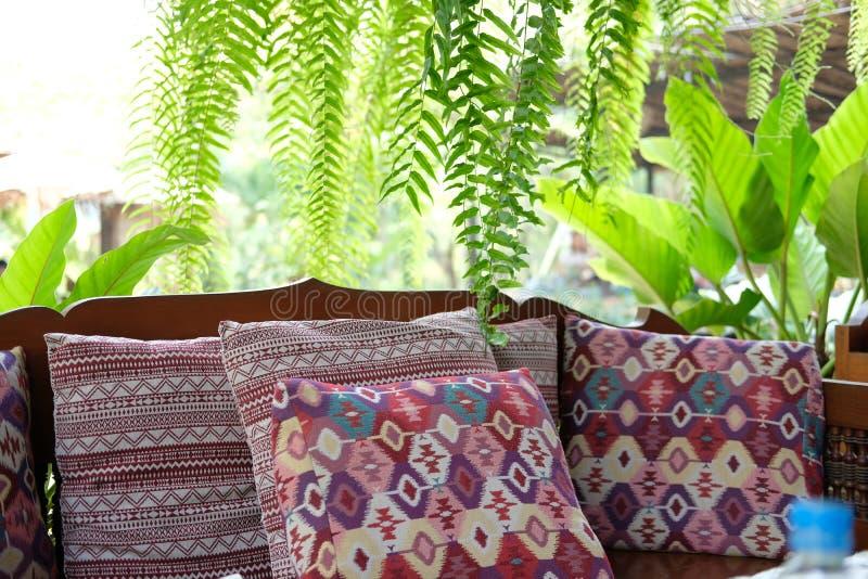 oreiller sur le banc en bois de canapé sur le patio de terrasse près du jardin images stock
