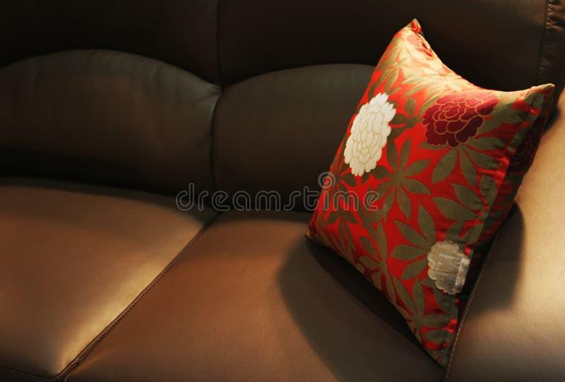 Oreiller sur un sofa en cuir photos libres de droits