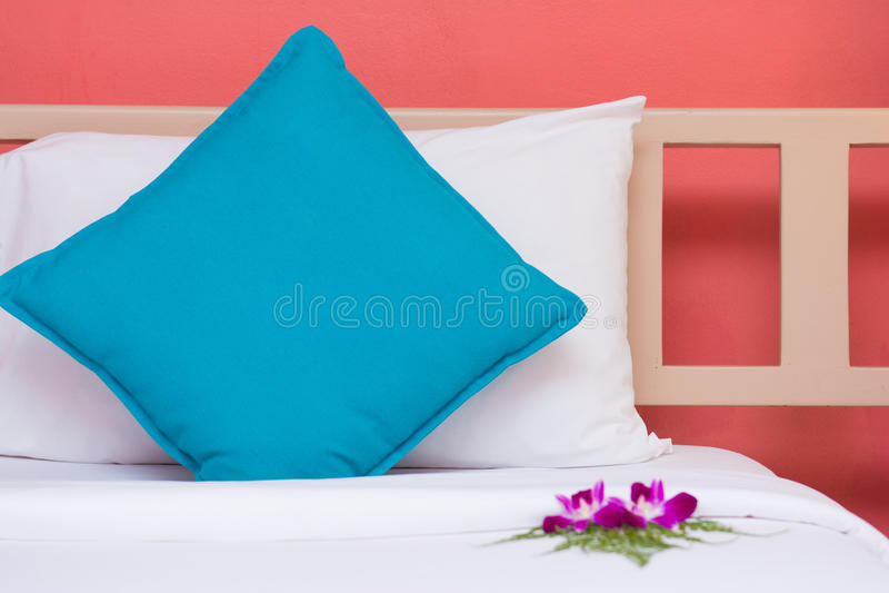 Oreillers blancs et bleus avec le fond orange de mur dans le bedroo images libres de droits