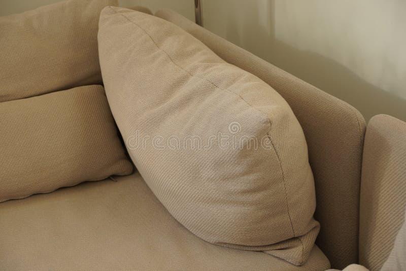 Oreillers bruns gris de tissu sur le divan photo stock