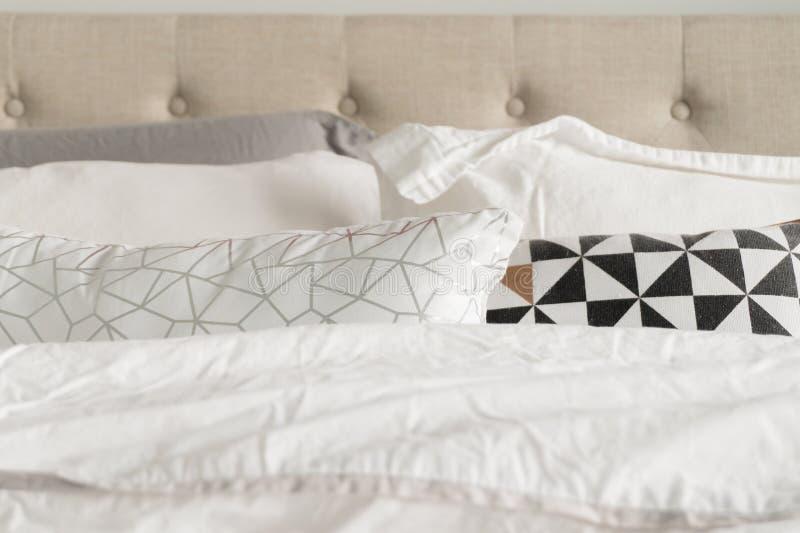Oreillers décoratifs de literie dans gris, blanc, noir, l'or et la literie blanche Tête de lit tuftée de tissu beige à l'arri photo libre de droits