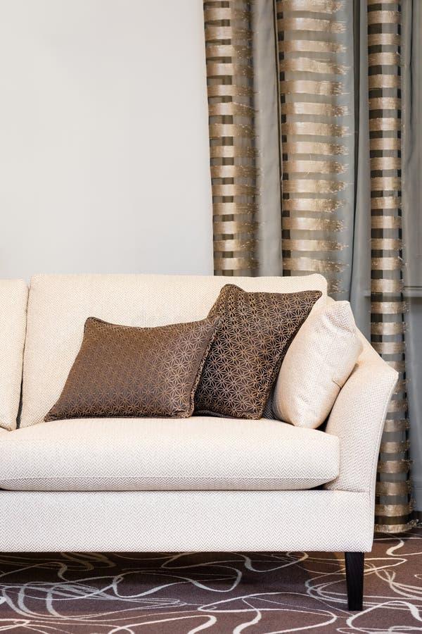 Oreillers de Brown sur le sofa beige vide photographie stock