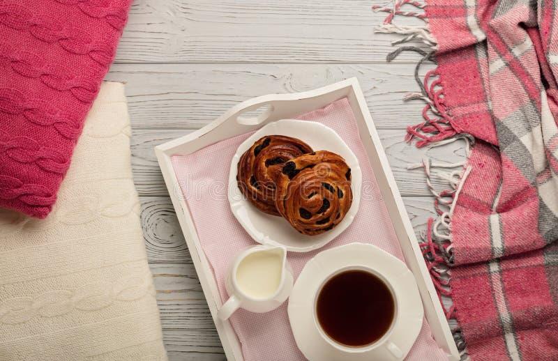 Oreillers et plaid tricoté, petits pains et café sur un CCB en bois léger images libres de droits