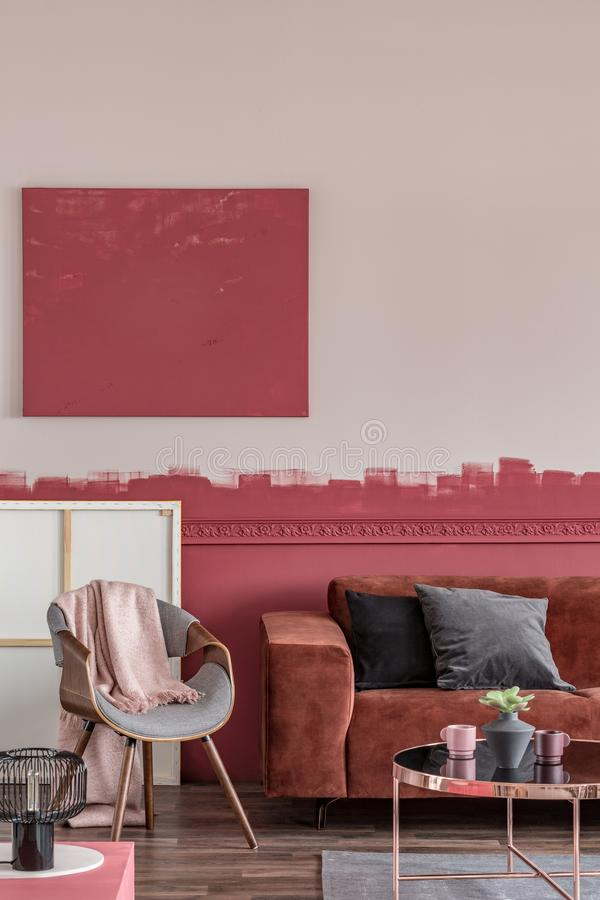Oreillers gris et noirs de velours sur le divan brun confortable dans le salon ?l?gant avec le mur blanc et rouge photographie stock