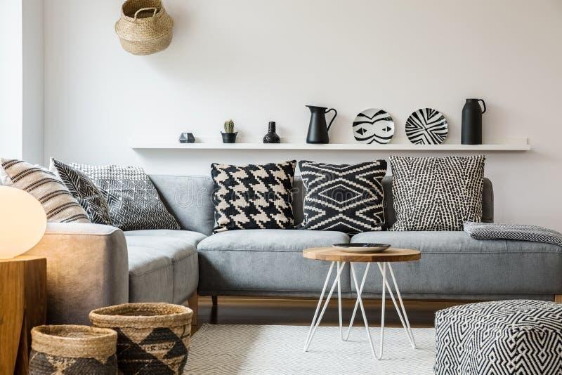 Oreillers modelés sur le divan gris dans le salon moderne W intérieur photo stock