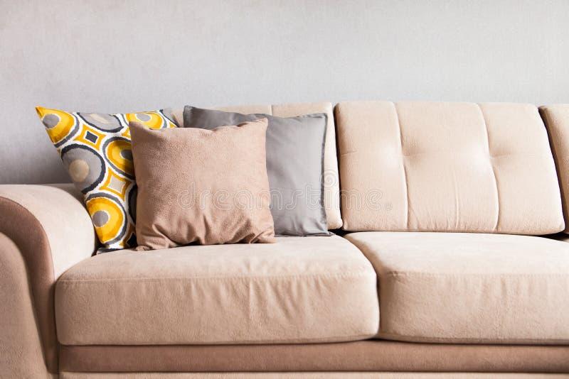 Oreillers multicolores sur un sofa beige de tissu, le concept du hom images libres de droits