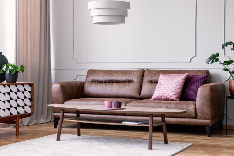 Oreillers sur le divan en cuir dans le rétro intérieur de salon avec la lampe au-dessus de la table en bois Photo réelle images libres de droits