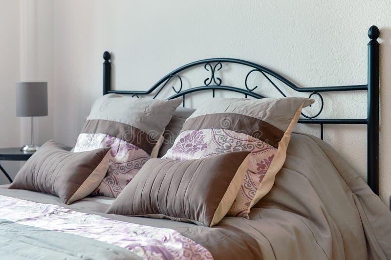 Oreillers sur le lit dans la chambre à coucher images stock