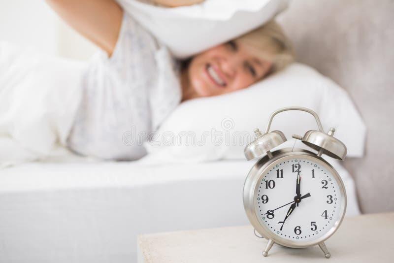 Oreilles de bâche de femme avec l'oreiller avec le réveil dans le premier plan images stock