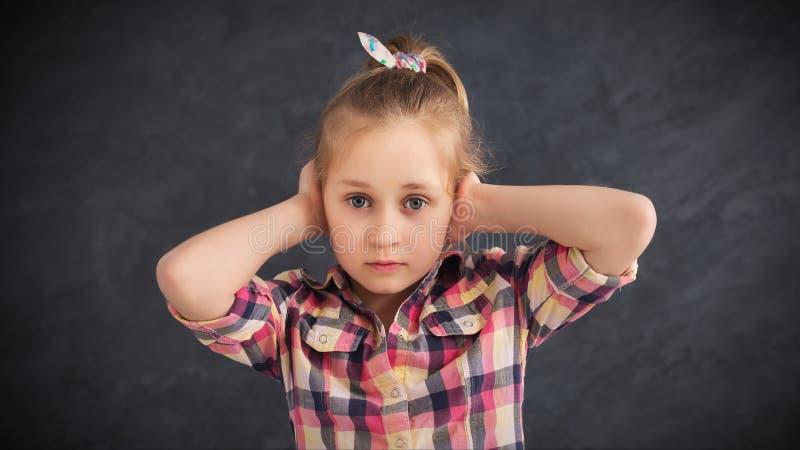 Oreilles de bâche de petite fille avec la main sur le fond gris photographie stock