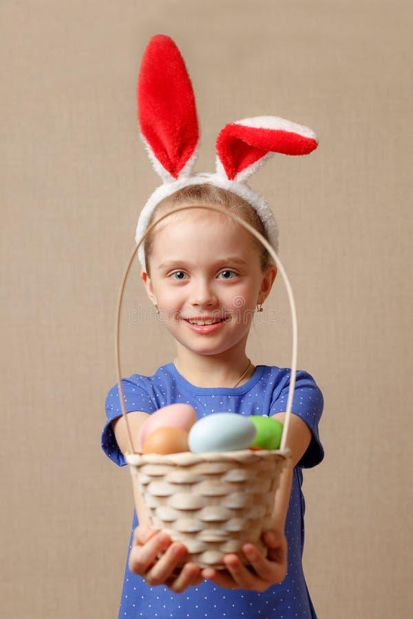 Oreilles de port adorables de lapin de petite fille jouant avec des oeufs de pâques images libres de droits