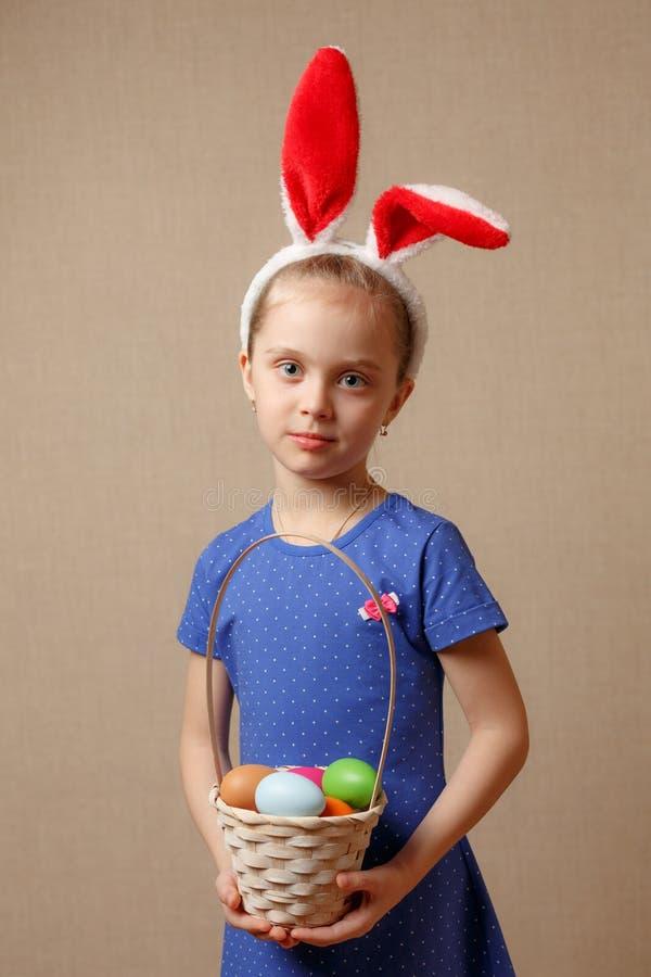 Oreilles de port mignonnes de lapin de petit enfant le jour de Pâques Fille tenant le panier avec les oeufs peints photographie stock