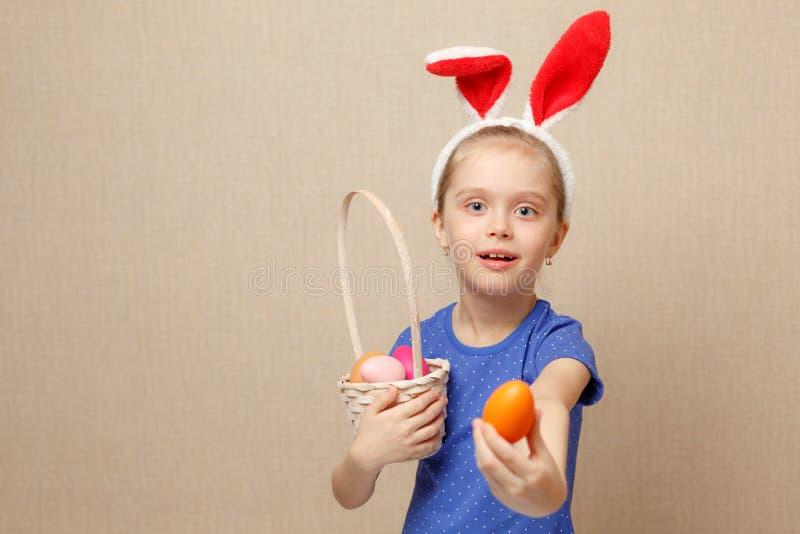 Oreilles de port mignonnes de lapin de petit enfant le jour de Pâques Fille tenant le panier avec les oeufs peints images stock