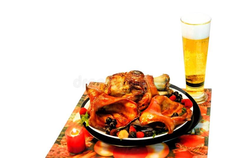 Oreilles et viande de rôti de porc d'un plat avec le persil, assaisonnement, baies d'isolement sur un fond blanc avec l'endroit p photos libres de droits