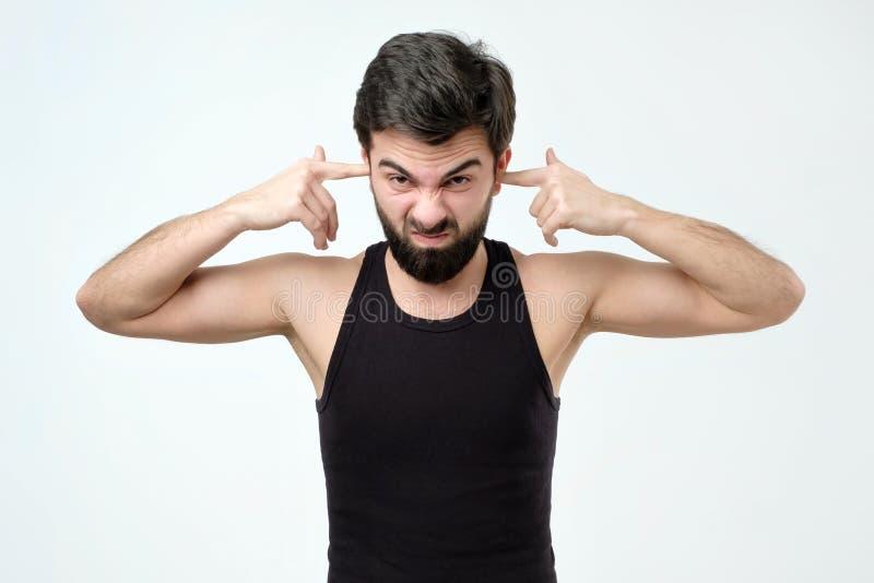 Oreilles se fermantes de jeune homme hispanique avec des doigts photos stock