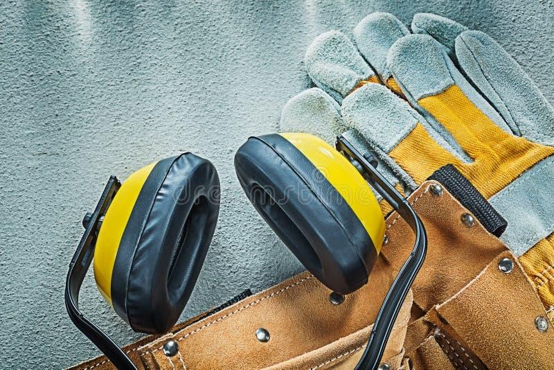 Orejeras de cuero de los guantes de la seguridad de la correa de la construcción en el CCB concreto fotos de archivo libres de regalías