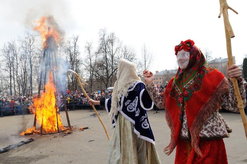 Orel, Rusland, 10 Maart, 2019: Maslenitsaselebration Meisjes in rood Slavisch Carnaval-kostuum en menigte van mensen met Dame stock afbeeldingen
