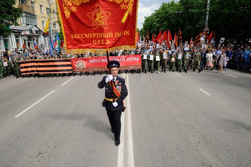 Orel, Rusland, 09 Mei, 2019: Victory Day, Onsterfelijke Regimentsparade Ambtenaar die met rode vlag vóór reusachtige menigte van  stock fotografie