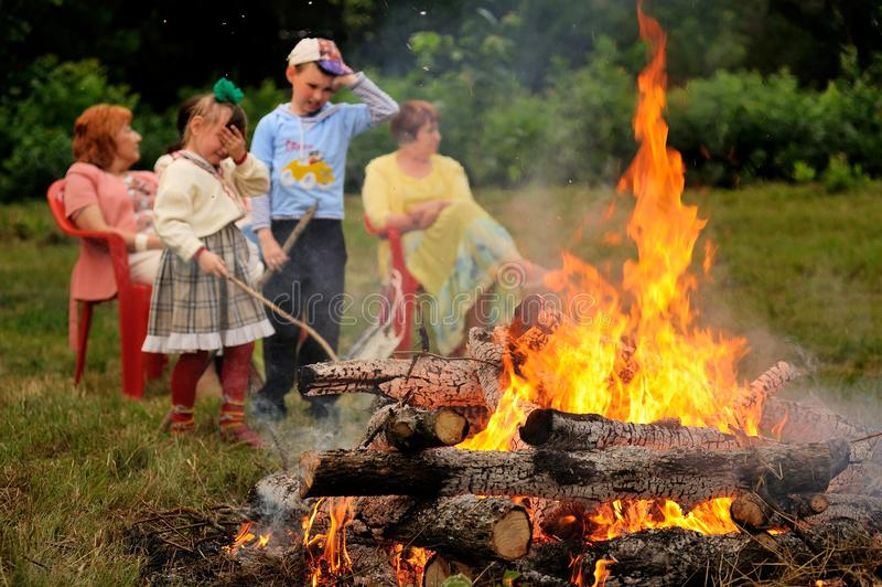Orel, Russia - June 19, 2015: Orlovskaya Mozaika music fest: chi. Ldren looking at bonfire horizontal stock image