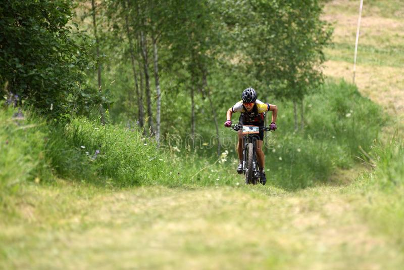 Orel, Russia, June 15, 2019: redBike Cup cross country cycle XCO competition. Young woman riding uphill at country road stock photo