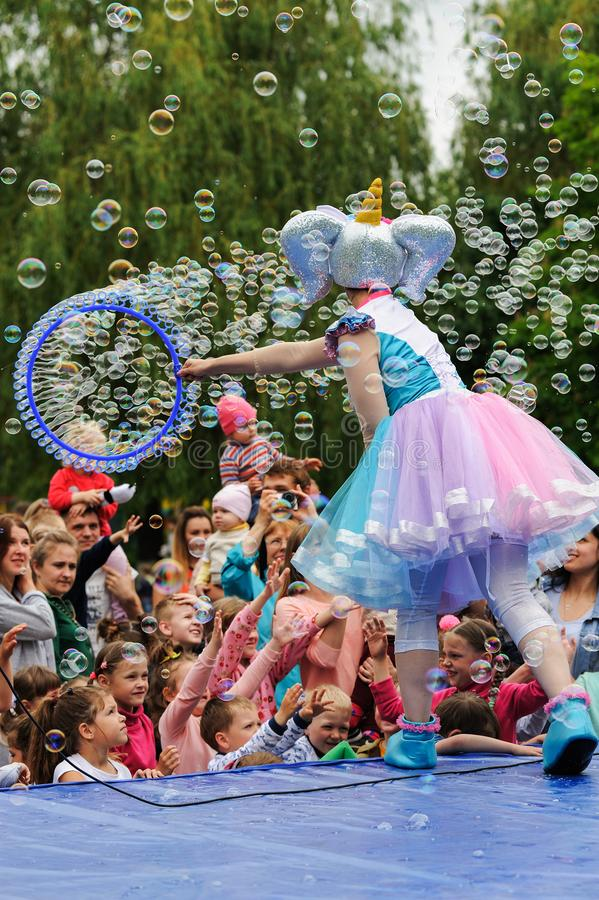 Orel, Russia, May 26, 2019: Twin Festival. Woman in bright fancy costume making many soap bubbles over crowd of children stock photo